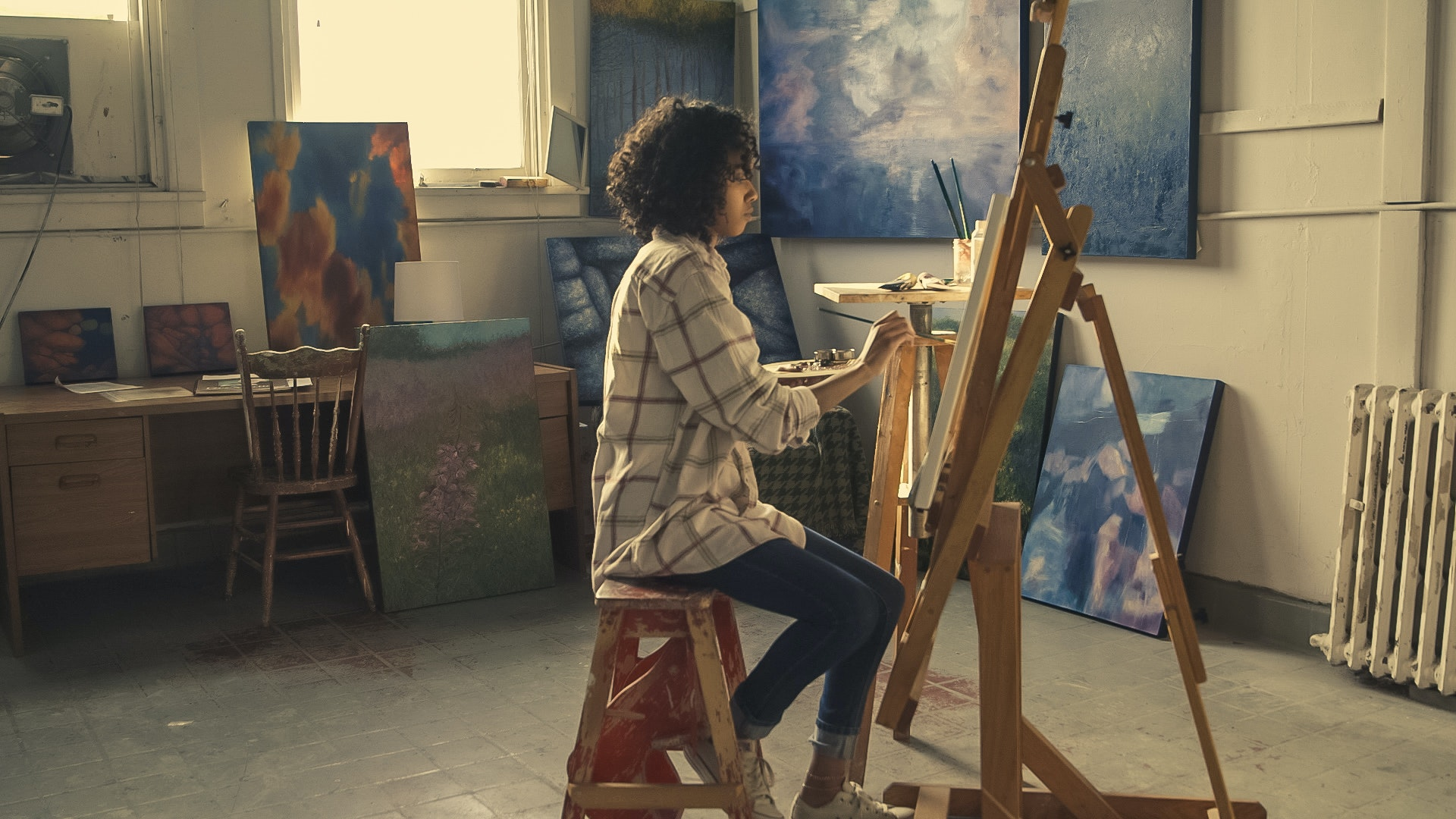 An artist painting on a canvas in her studio