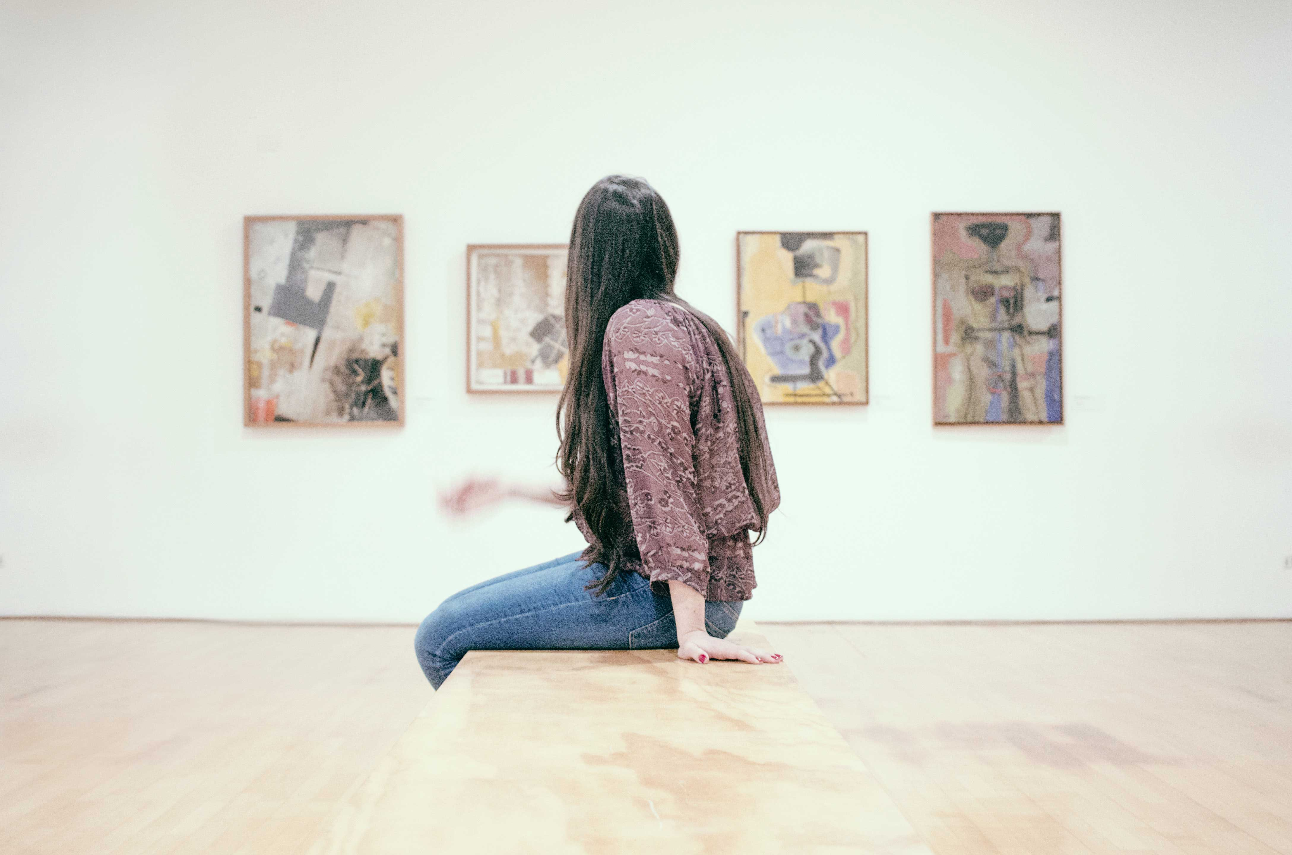 An artlover looking at paintings in an exhibition space